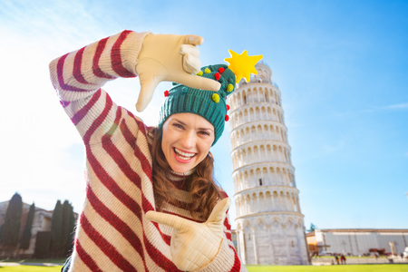 going for it: Young, itching from energy and searching for excitement. Im going to Christmas trip to Italy. It is a no-brainer. Happy woman in Christmas tree hat framing with hands in front of Leaning Tour of Pisa