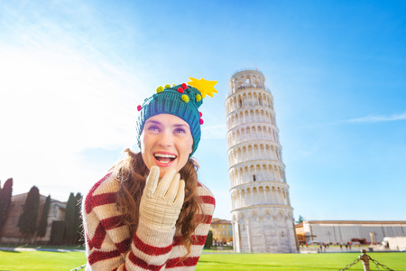 going for it: Young, itching from energy and searching for excitement. Im going to Christmas trip to Italy. It is a no-brainer. Woman in Christmas tree hat thinking about something in front of Leaning Tour of Pisa