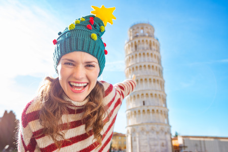 going for it: Young, itching from energy and searching for excitement. Im going to Christmas trip to Italy. It is a no-brainer. Happy woman in Christmas tree hat pointing on Leaning Tour of Pisa