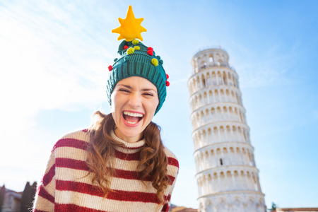 going for it: Young, itching from energy and searching for excitement. Im going to Christmas trip to Italy. It is a no-brainer. Portrait of happy woman in Christmas tree hat in front of Leaning Tour of Pisa
