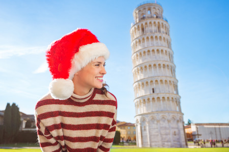 going for it: Young, itching from energy and searching for excitement. Im going to Christmas trip to Italy. It is a no-brainer. Happy woman in Santa hat looking on something in front of Leaning Tour of Pisa.