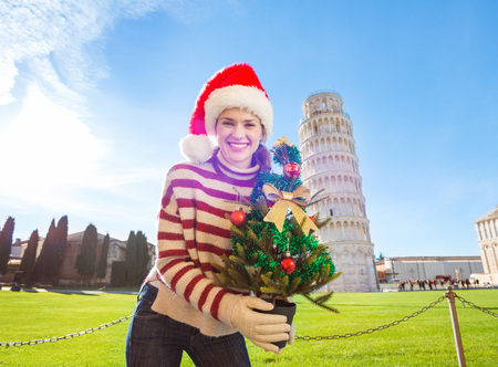 going for it: Young, itching from energy and searching for excitement. Im going to Christmas trip to Italy. It is a no-brainer. Happy woman in Santa hat holding Christmas tree in front of Leaning Tour of Pisa.