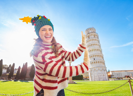 going for it: Young, itching from energy and searching for excitement. Im going to Christmas trip to Italy. It is a no-brainer. Smiling young woman in Christmas tree hat supporting Leaning Tour of Pisa