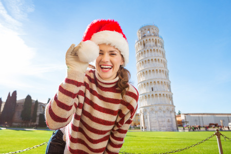 going for it: Young, itching from energy and searching for excitement. Im going to Christmas trip to Italy. It is a no-brainer. Happy woman playing with Santa hat in front of Leaning Tour of Pisa.