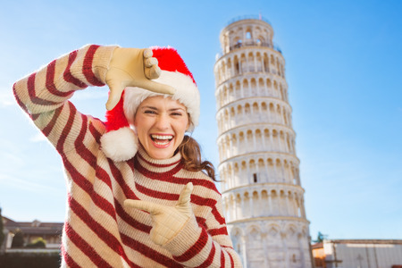 Young, itching from energy and searching for excitement. Im going to Christmas trip to Italy. It is a no-brainer. Smiling woman in Santa hat framing with hands in front of Leaning Tour of Pisa.