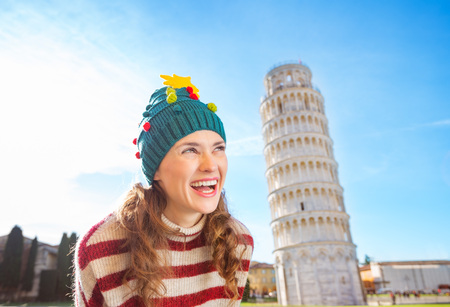 going for it: Young, itching from energy and searching for excitement.Im going to Christmas trip to Italy. It is a no-brainer.Happy woman in Christmas tree hat looking on something in front of Leaning Tour of Pisa Stock Photo