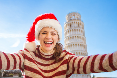 going for it: Young, itching from energy and searching for excitement. Im going to Christmas trip to Italy. It is a no-brainer. Happy woman in Santa hat taking selfie in front of Leaning Tour of Pisa. Stock Photo