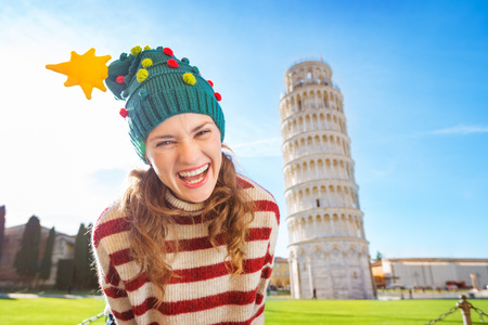going for it: Young, itching from energy and searching for excitement. Im going to Christmas trip to Italy. It is a no-brainer. Portrait of merry young woman in Christmas tree hat in front of Leaning Tour of Pisa Stock Photo