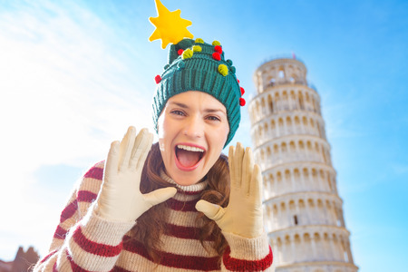 going for it: Young, itching from energy and searching for excitement. Im going to Christmas trip to Italy. It is a no-brainer. Happy woman in Christmas tree hat shouting in front of Leaning Tour of Pisa