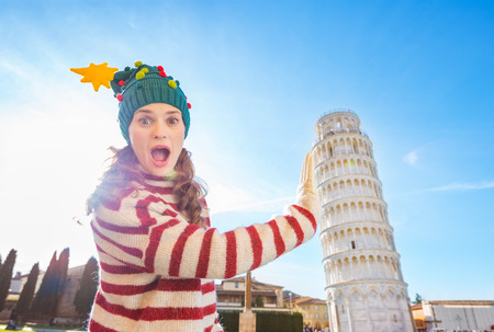 going for it: Young, itching from energy and searching for excitement. Im going to Christmas trip to Italy. It is a no-brainer. Surprised young woman in Christmas tree hat holding Leaning Tour of Pisa Stock Photo