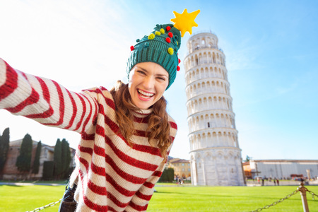 going for it: Young, itching from energy and searching for excitement. Im going to Christmas trip to Italy. It is a no-brainer. Happy woman in Christmas tree hat taking selfie in front of Leaning Tour of Pisa Stock Photo