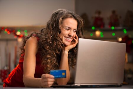 enjoyable: Christmas holidays are a time of gift-giving. Online shopping can make Christmas season less stressful and more enjoyable. Happy young woman holding credit card and choosing gifts on laptop