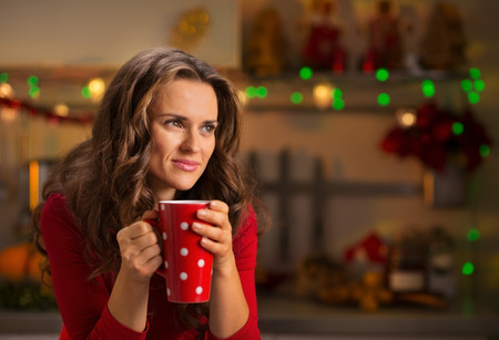 female christmas: A little Christmas treats are wonderful way to enjoy the spirit of the season. Thoughtful woman having a cup of hot chocolate with marshmallows and looking sideways in Christmas decorated kitchen Stock Photo