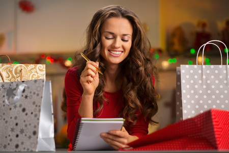 christmas list: Christmas holidays are a time of gift-giving. Shopping list can make Christmas season easy and save time for more fun. Happy young woman among shopping bags with pen and notebook checking list