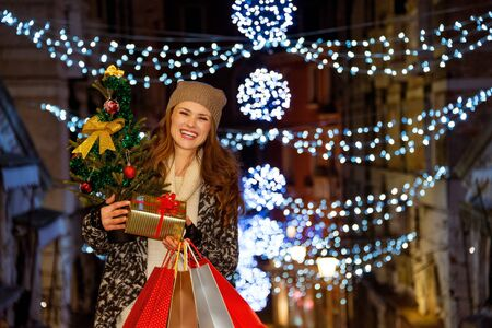 shopping trip: This Christmas is crushing on fashion forward shopping. Portrait of stylishly dressed smiling young woman holding Christmas tree, gift and shopping bags while standing among Christmas lights