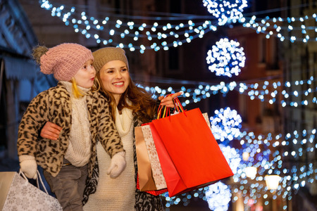 to the point: Holiday family trip to Venice, Italy can change the whole Christmas experience. Mother with shopping bags pointing on something to child while on Rialto Bridge in the evening among Christmas lights Stock Photo