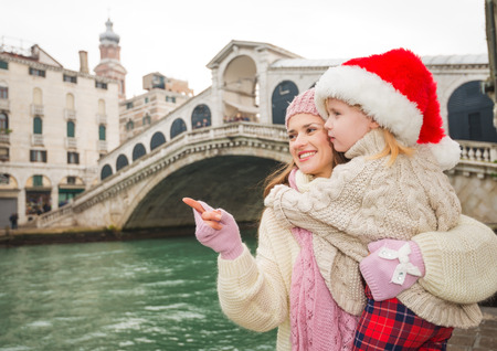 another way: Small family trip is another way how to make Christmas holidays even more appealing. Happy mother pointing on something to child wearing Santa Hat while standing in the front of Ponte di Rialto Stock Photo