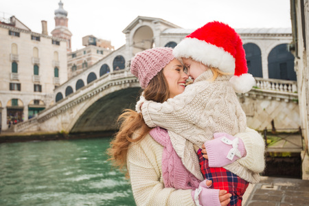 another way: Small family trip is another way how to make Christmas holidays even more appealing. Happy mother and child in Santa Hat hugging in the front of Ponte di Rialto