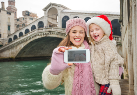 another way: Small family trip is another way how to make Christmas holidays even more appealing. Happy mother and child in Santa Hat taking selfie with smartphone in front of Ponte di Rialto