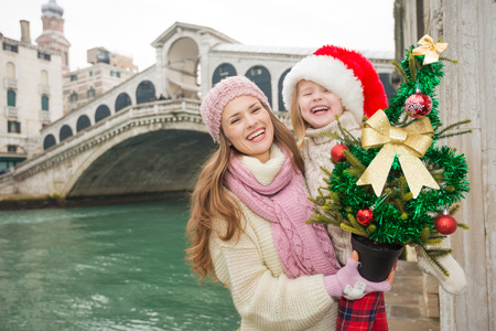 another way: Small family trip is another way how to make Christmas holidays even more appealing. Happy mother and child in Santa Hat with Christmas tree in the front of Ponte di Rialto
