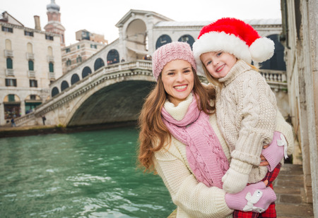 another way: Small family trip is another way how to make Christmas holidays even more appealing. Portrait of happy mother and child in Santa Hat in the front of Ponte di Rialto