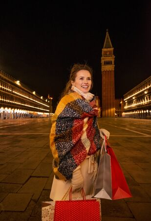 desirable: So desirable winter season sales in charming Venice, Italy. Happy woman in winter coat holding shopping bags and looking into distance while standing on Piazza San Marco in the evening Stock Photo