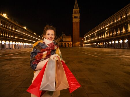 So desirable winter season sales in charming Venice, Italy. Smiling woman in winter coat holding shopping bags while standing on Piazza San Marco in the evening Stock Photo