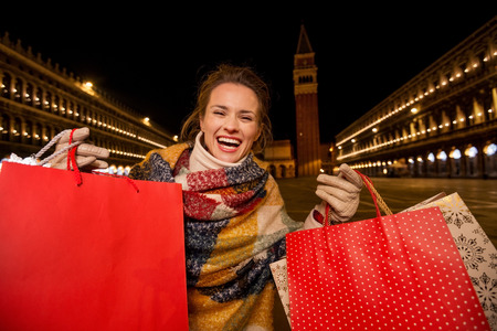 female shopper: So desirable winter season sales in charming Venice, Italy. Portrait of excited woman in winter coat showing shopping bags while standing on Piazza San Marco in the evening
