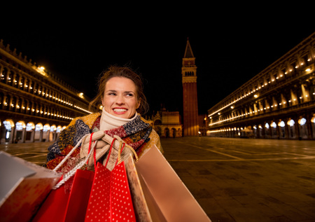 desirable: So desirable winter season sales in charming Venice, Italy. Happy woman in winter coat holding shopping bags and looking on copy space while standing on Piazza San Marco in the evening