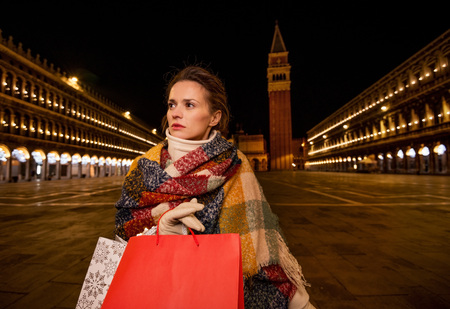 desirable: So desirable winter season sales in charming Venice, Italy. Modern woman in winter coat holding shopping bags and looking into distance while standing on Piazza San Marco in the evening