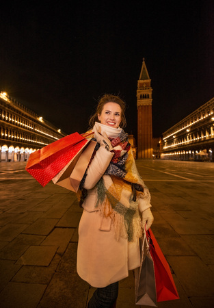 desirable: So desirable winter season sales in charming Venice, Italy. Playful woman in winter coat holding shopping bags and looking on something while standing on Piazza San Marco in the evening