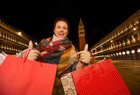 desirable: So desirable winter season sales in charming Venice, Italy. Happy woman in winter coat holding shopping bags and showing thumbs up while standing on Piazza San Marco in the evening Stock Photo