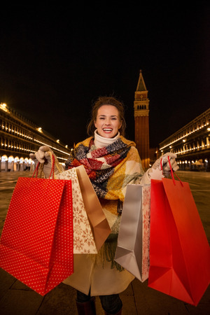 desirable: So desirable winter season sales in charming Venice, Italy. Happy woman in winter coat showing shopping bags while standing on Piazza San Marco in the evening