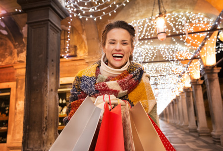 excitement: It is time for fashion forward shopping for a most desirable Christmas gifts in Venice, Italy. Excited woman with shopping bags standing under Christmas light in the evening Stock Photo