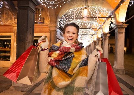 desirable: It is time for fashion forward shopping for a most desirable Christmas gifts in Venice, Italy. Excited woman with shopping bags standing under Christmas light in the evening Stock Photo