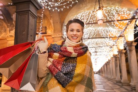 desirable: It is time for fashion forward shopping for a most desirable Christmas gifts in Venice, Italy. Smiling woman with shopping bags standing under Christmas light in the evening