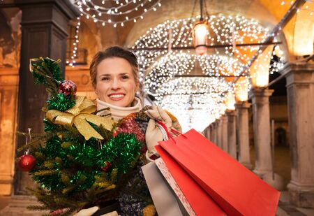 desirable: It is time for fashion forward shopping for a most desirable Christmas gifts in Venice, Italy. Happy woman holding Christmas tree and shopping bags and looking into distance under Christmas lights Stock Photo