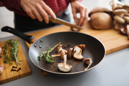 Fresh sliced mushrooms are sitting in a pan on a wooden board, ready to be put on the stove. In the background, a woman slices more fresh mushrooms.