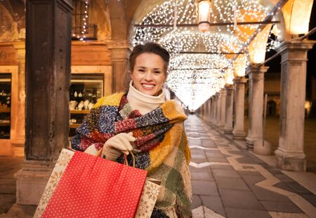 desirable: It is time for fashion forward shopping for a most desirable Christmas gifts in Venice, Italy. Portrait of happy woman with shopping bags standing under Christmas light in the evening