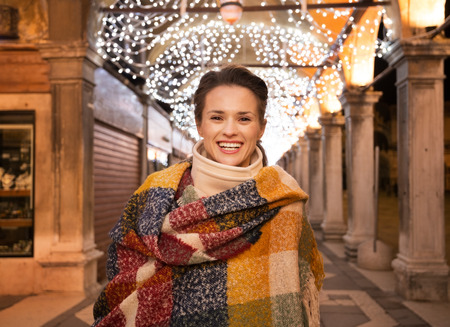 desirable: It is time for fashion forward shopping for a most desirable Christmas gifts in Venice, Italy. Portrait of happy woman standing under Christmas light in the evening