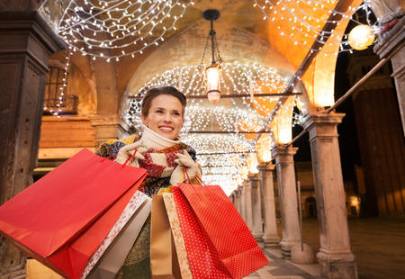 desirable: It is time for fashion forward shopping for a most desirable Christmas gifts in Venice, Italy. Happy woman with shopping bags looking into distance while standing under Christmas light in the evening