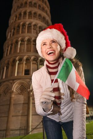 adds: The iconic Italian architecture adds style to the Christmas celebration. Happy young woman in Santa hat with Italian flag looking up in the front of Leaning Tower of Pisa, Italy in the evening Stock Photo