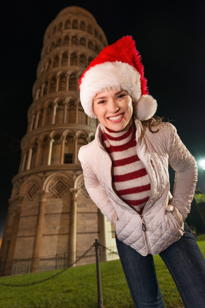italian architecture: The iconic Italian architecture adds style to the Christmas celebration. Portrait of smiling young woman in Santa hat standing in the front of Leaning Tower of Pisa, Italy in the evening