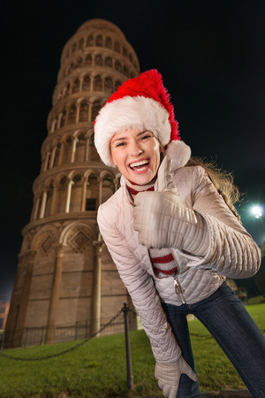 italian architecture: The iconic Italian architecture adds style to the Christmas celebration. Happy young woman in Santa hat showing thumbs up in the front of Leaning Tower of Pisa, Italy in the evening