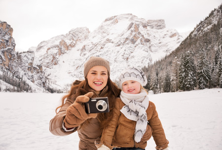 winter photos: Winter leisure time spent outdoors among snowy peaks can turn the holidays into a fascinating journey. Happy mother and child taking photos outdoors among snow-capped mountains