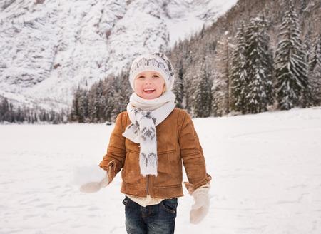 Hiver temps de loisirs passé à l'extérieur entre les sommets enneigés peut transformer les vacances dans un voyage fascinant. Happy child tenant boule de neige tout en se tenant à l'extérieur dans les montagnes enneigées