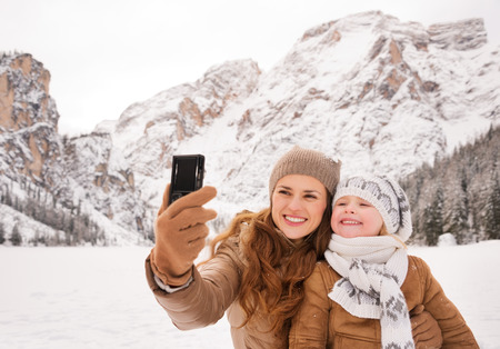 Winter leisure time spent outdoors among snowy peaks can turn the holidays into a fascinating journey. Mother and child taking selfie outdoors among snow-capped mountains Stock Photo