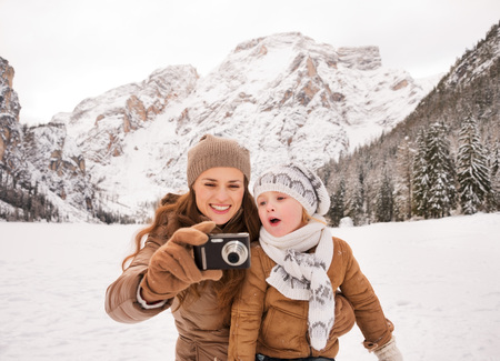 winter photos: Winter leisure time spent outdoors among snowy peaks can turn the holidays into a fascinating journey. Mother and surprised child checking photos in camera outdoors among snow-capped mountains
