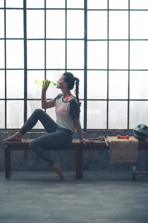 window bench: A barefoot, fit woman in workout gear is sitting on a bench by the window in a loft gym, drinking refreshing water after a good workout.