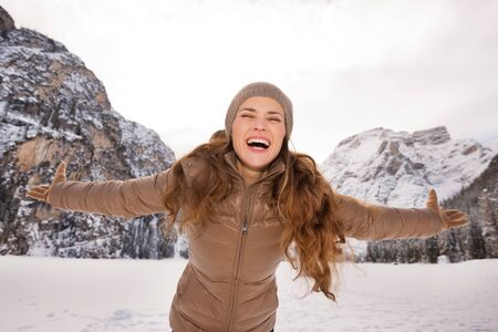 rejoicing: Energy-filling and exciting winter weekends in the mountains. Portrait of happy young woman rejoicing outdoors among snow-capped mountains Stock Photo